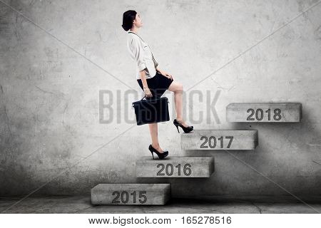 Image of a female worker climbing upward on the stairs toward numbers 2017