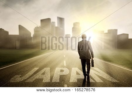 Young male manager carrying a briefcase while walking toward a city with word of Japan on the road