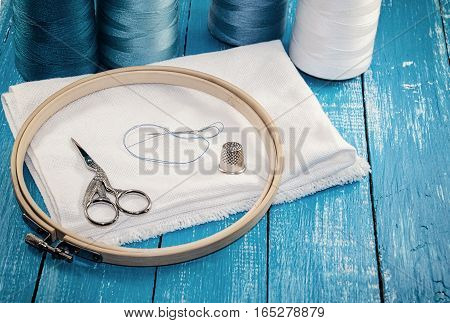 Threads in spools with white cloth for the embroidery and sewing blue gamma vintage styling