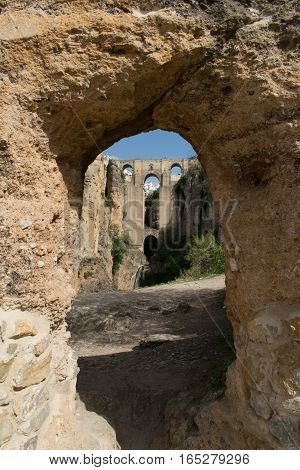 a photo taken through an archway at the bridge at Ronda, Spain