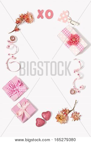 Composition to Valentines Day: gift boxes with bows flowers tape little hearts XO letters denoting kisses and hugs. All gifts pink. The mood of love and tenderness. Flat lay top view