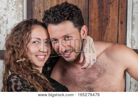 Young happy couple hugging smiling. Athletic handsome bearded man and young pretty woman laughing having clamped their teeth straw outdoors in summer loving married pair closeup