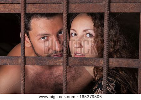Portrait of a young couple in jail loving man and woman looking out of rusty iron rods