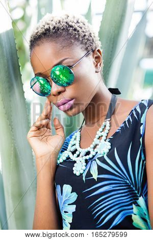 Young beautiful African fashion model in traditional dress.Afro-American fashion model posing in the jungle. Beautiful black woman with glossy makeup