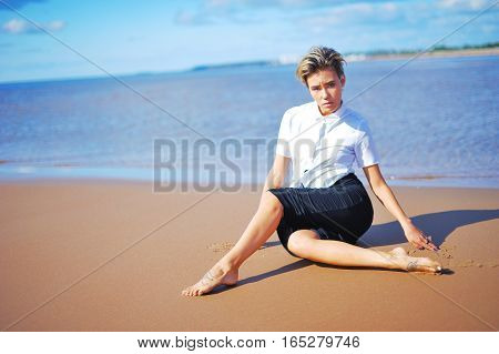 Beautiful portrait of a young attractive girl posing on the beach sitting on the sand near the water with open legs. Model looking at the camera.