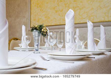 White and yellow restaurant interior. Napkins tubes rolls on plates.