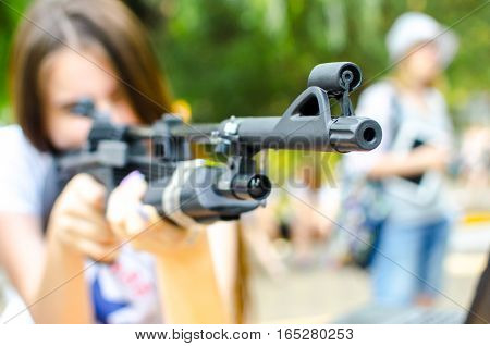 Girl looking to the sight air rifle outdoors