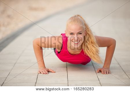 Woman Doing Pushups On A Path Near A Sea
