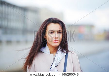 Portrait of a young beautiful confident woman in elegant coat for the urban landscape