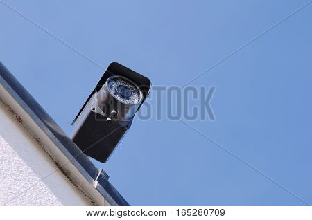 Security Camera Closeup Bottom View with Clear Blue Sky Daytime