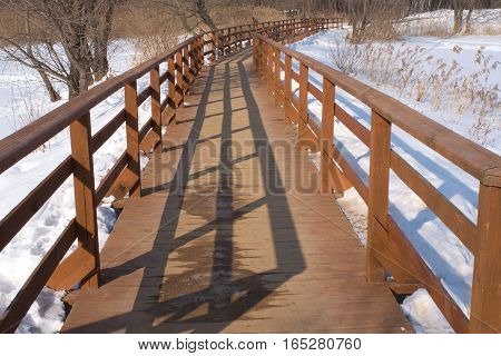 Winter landscape with long wooden pedestrian bridge