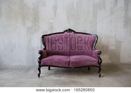 Purple vintage sofa on a gray background