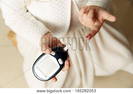 Medicine, diabetes, glycemia, health care and people concept - close up of man hands checking blood sugar level by Glucose meter