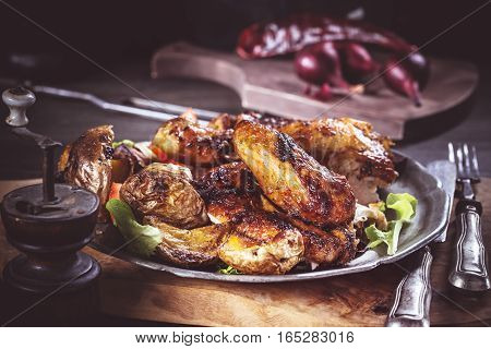 Slices of grilled chicken on plate in rural setting. Dark toned