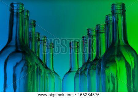 A dozen crystal bottlenecks of empty glass wine bottles standing in line on green background