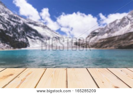 Wooden board empty table in front of blurred background. Perspective brown wood over lake in snow mountain for mock up display or montage your products vintage.