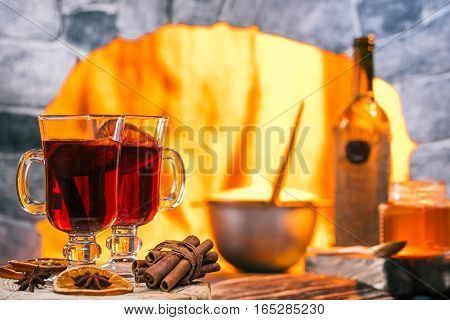 Mulled wine in irish glasses. Wine bottle and honey on the middle ground. Pan in hearth on the background
