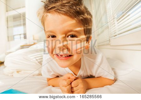 Close-up portrait of happy six years old boy laying in his bed at home in sunny morning