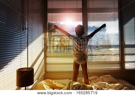 Picture of little boy standing on his bed and looking out the window in sunny morning