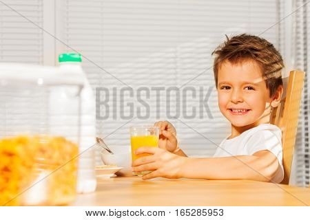 Side view portrait of happy Caucasian boy holding glass with orange juice at breakfast in the kitchen