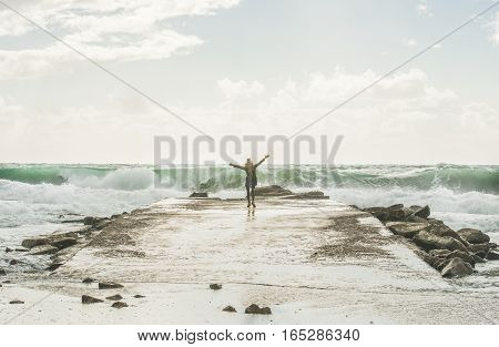Young woman tourist standing on pier and enjoying waves of stormy Mediterranean sea in winter with raised hands, Alanya, Turlkey