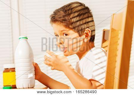 Side view portrait of little boy drinking milk during breakfast in morning