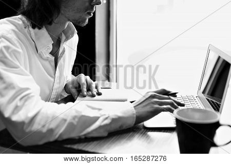 young businessman or student sitting and working near window with open laptop black and white color