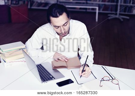 Businessman or university student smiling working on laptop reading a book in a library
