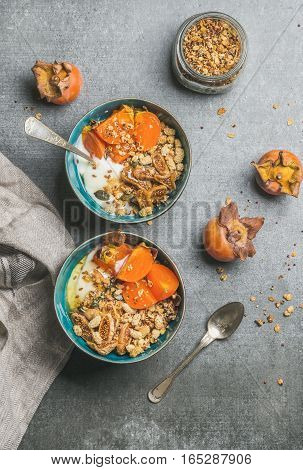 Healthy vegetarian breakfast. Oatmeal, quinoa granola with yogurt, dried fruit, seeds, honey, fresh persimmon in blue ceramic bowls over grey background, top view. Dieting, allergy-friendly concept