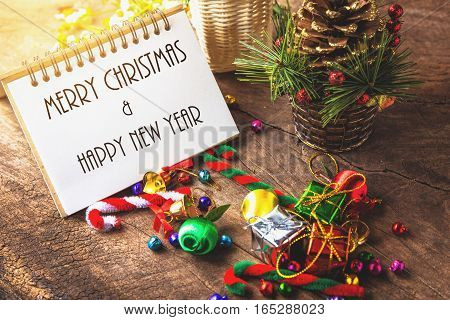 Merry christmas and Happynew year text on blank notebook with gift box daisy flower candy ball and cane pine decoration on vintage wooden background.