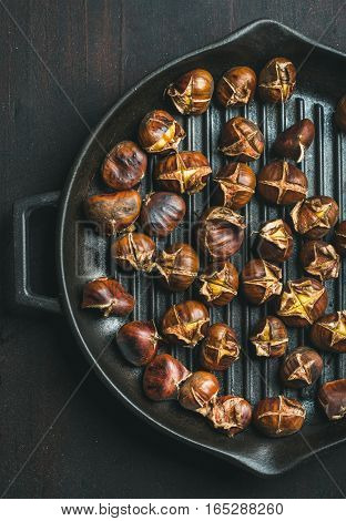 Roasted chestnuts in cast iron grilling pan over dark wooden background, top view, vertical composition
