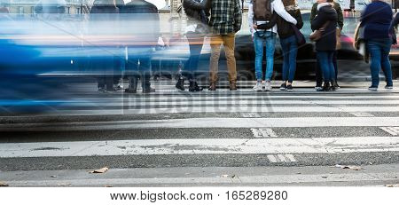 people waiting at the pedestrian crossing with car traffic in motion blur