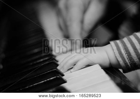 Close up hands of little girl playing the piano with defocused adults hands on the background