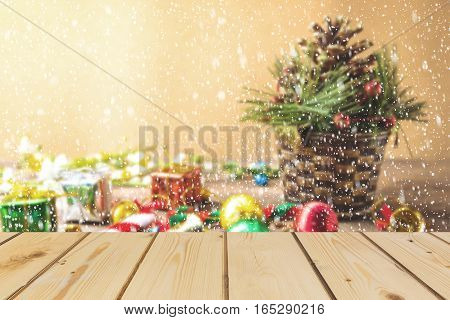 Wooden board empty table in front of blurred snow background of Christmas concept with pine cane gift box candy balls for mock up display or montage your products vintage.
