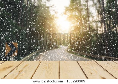 Wooden board empty table in front of blurred background. Perspective brown wood over road in forest with snow for mock up display or montage your products vintage.