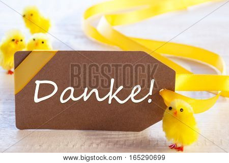 Label With German Text Danke Means Thank You. Easter Decoration Like Chicks. White Wooden Background. Card For Seasons Greetings