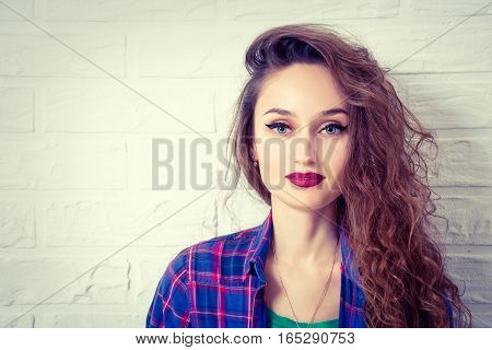 Portrait of Hipster Girl in Checked Shirt on White Brick Wall Background. Trendy Casual Fashion Woman Makeup. Beautiful Glamour Female. Toned Photo with Copyspace.