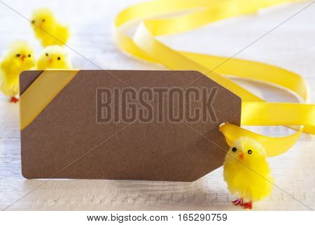 Label With Copy Space For Advertisement. Easter Decoration Like Chicks. White Wooden Background. Card For Seasons Greetings