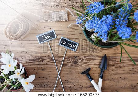Two Signs With German Text Zeit Fuer Mich Means Time For Me. Sunny Spring Flowers Like Grape Hyacinth And Crocus. Gardening Tools Like Rake And Shovel. Hemp Fabric Ribbon. Aged Wooden Background