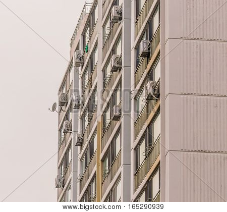 Exterior of an apartment building with air conditioning units installed on the outside wall of each apartment