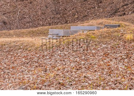 Burial mound with concrete markers in a wooded area