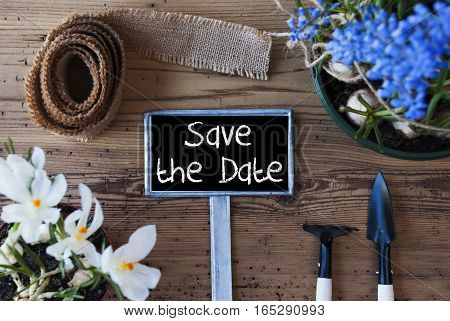 Sign With English Text Save The Date. Spring Flowers Like Grape Hyacinth And Crocus. Gardening Tools Like Rake And Shovel. Hemp Fabric Ribbon. Aged Wooden Background