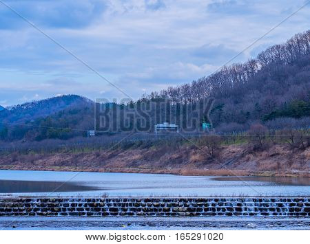 Rural landscape of small waterfall in a river with foothills and a country road in the background and a beautiful blue sky with puffy white clouds