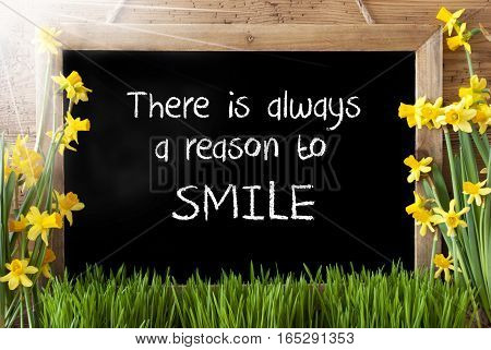 Blackboard With English Quote There Is Alwyas A Reason To Smile. Sunny Spring Flowers Nacissus Or Daffodil With Grass. Rustic Aged Wooden Background.
