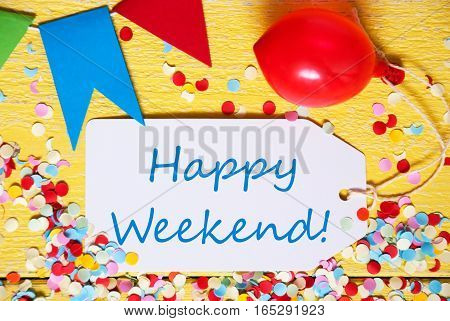 White Label With English Text Happy Weekend. Close Up Of Party Decoration Like Streamer, Confetti And Balloon. Flat Lay Or Top View. Yellow Wooden Background