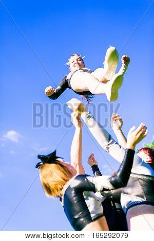A team of pretty, female cheerleaders having fun outdoors.