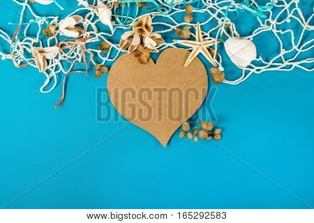 brown heart in  nautical net with starfish and seashell on turquoise painted wood