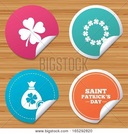 Round stickers or website banners. Saint Patrick day icons. Money bag with coin and clover sign. Wreath of quatrefoil clovers. Symbol of good luck. Circle badges with bended corner. Vector