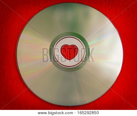 Red Valentine's day background - colorful CD disk with heart shape in the central part