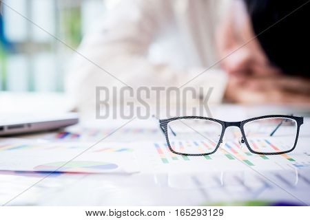 Tired Businessman Sleeping While Calculating Expenses At Desk In Office